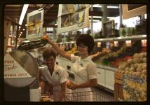 Two ladies work at the grocery store. Los Angeles. 1965.