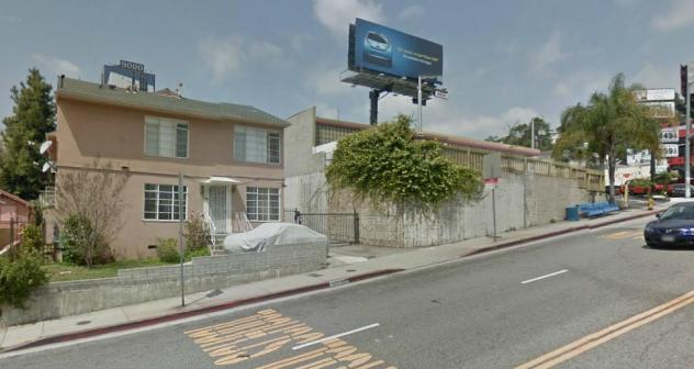 The two-story stucco apartment not mint green anymore. You're standing on San Vincente. There's the gas station on the right (Sunset Blvd)